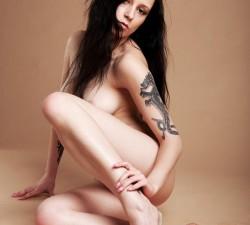 morena desnuda luciendo sus tatuajes